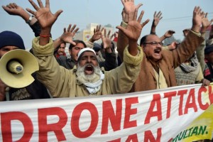 People hold a banner as they shout slogans during a protest against a U.S drone attack.