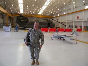 An Oregon Army National Guard reconnaissance drone on the flight line in a hanger in Pendleton is dwarfed by Guard spokesman Pat Caldwell and a combat-ready Chinook helicopter. The RQ7B Shadow drones are now based at the Guard's armory at the Eastern Oregon Regional Airport and will be used to train operators for combat missions abroad.